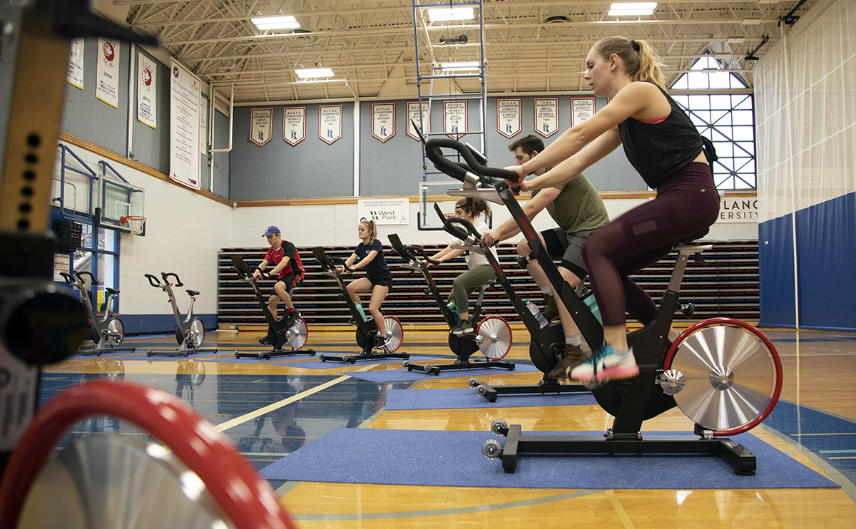 Students and faculty in spin class in a gymnasium